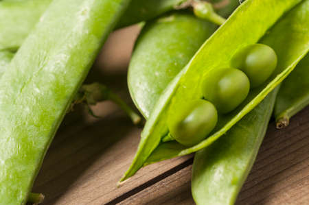 sweet sugar snap: green peas in pods freshly picked on wood