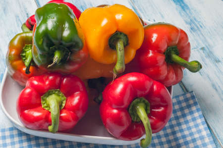 presented: green red and yellow peppers presented on white tray