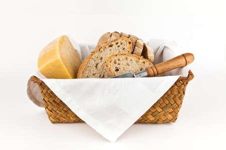 canasta de panes: El pan tradicional y queso sobre fondo blanco.