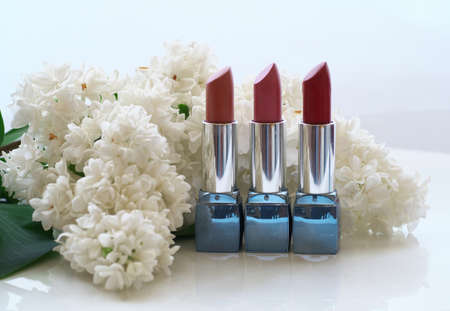 cosmetics and lilac blossom tube Lipstick on white Lilac flowers background.