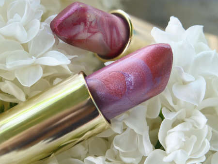 grease paint: cosmetics and lilac blossom tube perl Lipstick on white Lilac flowers background. Stock Photo