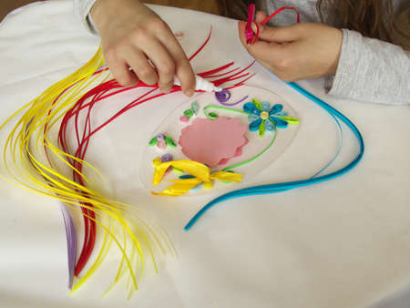 Decorate with strips of paper, quilling .Hands child while creative work making decorations paper. Standard-Bild