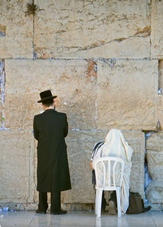 Two orthodox men praying in front of the wailing wall photo