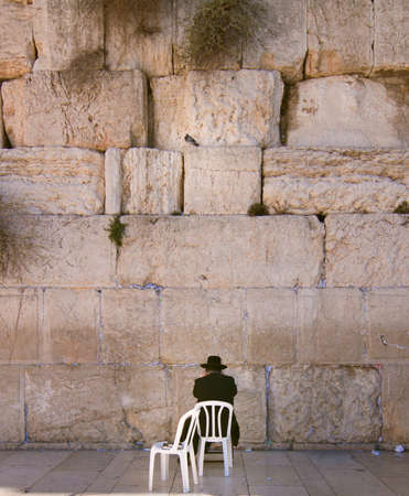 One orthodox man praying in front of the wailing wall photo