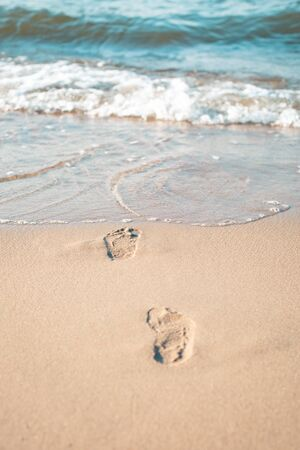 Footprints from children's feet in the clear sea sand
