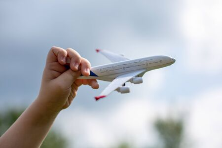 Little child's hand holds white metal airplane model pretending he is flying Boing plane in clear blue sky with clean white fluffy clouds.