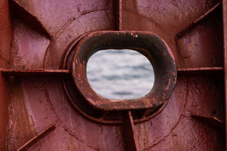 An empty haws in an old red rusted ship hull overlooking the sea