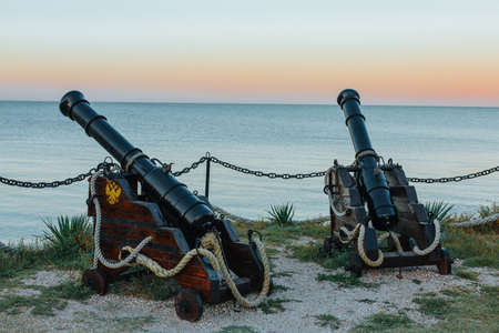 Two old Russian cannons are directed towards the sea from the shore