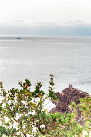 Two tourist sitting on rocky cliff and enjoying beautiful seaview