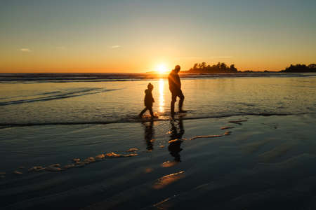 beachcombing: Father and son walking in the surf at Chesterman Beach in Tofino, British Columbia Stock Photo