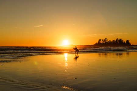 beachcombing: Surfer at sundown at Chesterman Beach in Tofino, British Columbia, Canada