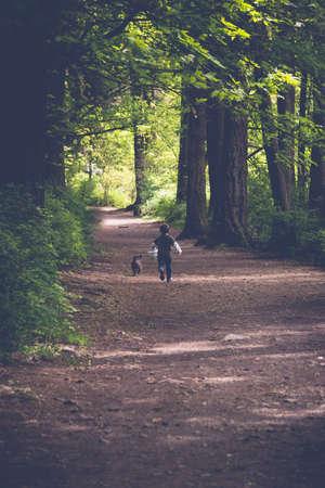 Junge, der Wald in Victoria, Britisch-Columbia mit seinem Hund erforscht Standard-Bild - 57772217