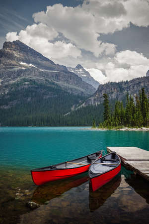 rockies: Red canoes seem perfectly placed and waiting at Lake OHara in Yoho National Park, Canadian Rockies, British Columbia Stock Photo