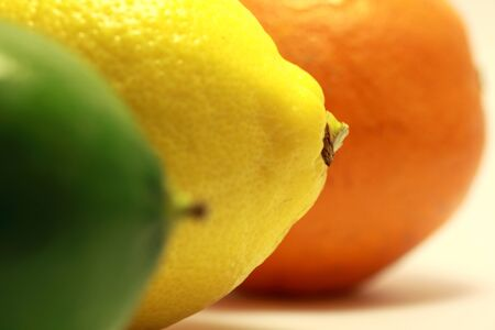 Close up of a lime a lemon and an orange, with the focus on the lemon