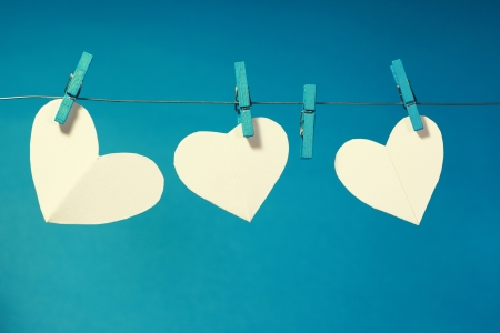 infatuation: Three paper hearts pegged on a line with a blue background  One heart is missing  Stock Photo