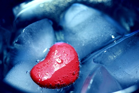 Plasticine heart lodged on some ice, symbolizing an icy love  photo