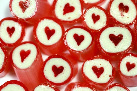 Close up of red and white candy pieces with red heart in the centre