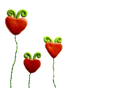 A family of three red heart flowers on a white background.
