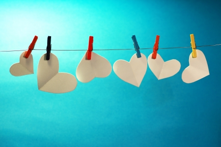 Paper hearts on a miniature clothes line, symbolizing putting your heart on the line. photo
