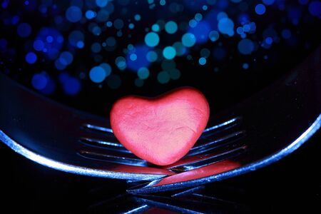 Two forks joined with a heart sitting between them on a bokeh background. Stock Photo