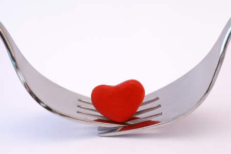 Symbolising romantic meal for two with two forks and a red heart on a white background. photo