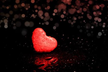 Red plasticine heart alone on a black bokeh background.