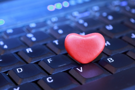 finding love: Red plasticine heart sitting on a computer keyboard. Stock Photo