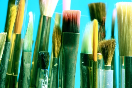 Series of paintbrushes on blue background.