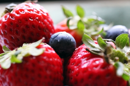 Close up of strawberries and blueberries in a bowl.