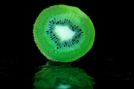 Sliced Kiwifruit on a reflective black background Stock Photo - 17045100
