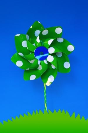 Green pinwheel representing a wind turbine on a grassy hill