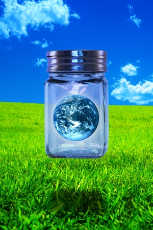 Floating earth in a floating glass jar in a green field against a blue sky Stock Photo - 17106126