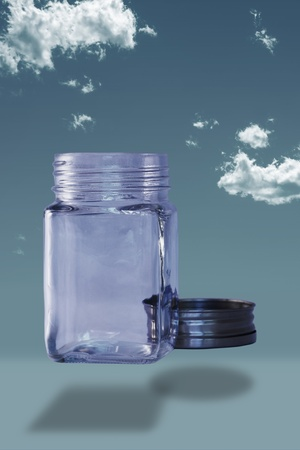 Empty bottle with lid off on a blue sky background Stock Photo - 17106119