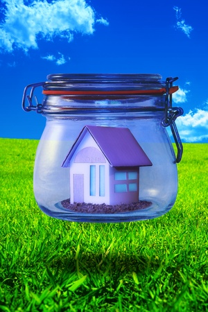 Miniature home enclosed in a floating glass jar on a grassy field with a blue sky background