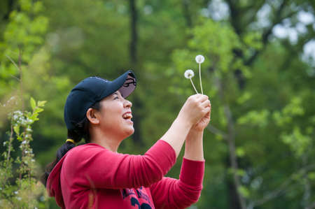 A smiling woman grabbing dandelion 스톡 콘텐츠