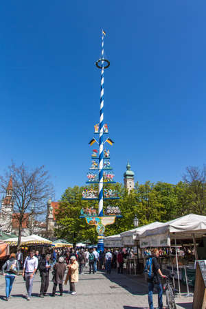maypole: Maypole at Viktualienmarkt with people passing by