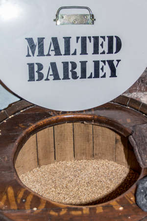 malted: Brown barrel of malted barley on the tour through the Old Jameson Distillery in Dublin