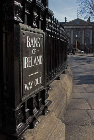 regent: Entrance of Bank of Ireland in Dublin with the way out sign and black iron bars, view on the Regent House Stock Photo