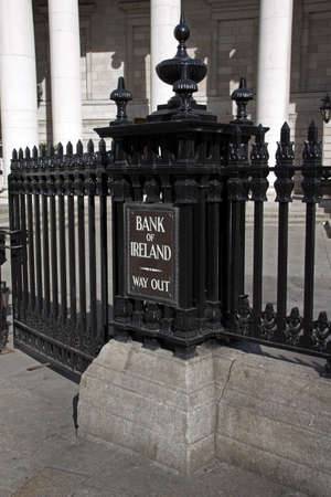 way out: Entrance of Bank of Ireland in Dublin with the way out sign and black iron bars