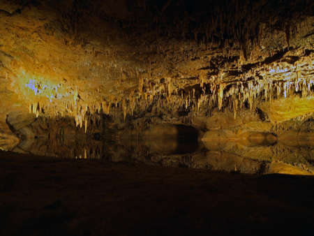 realm: Large cave in Luray Caverns in Luray Virginia USA with reflections in the water of several spikes stalactites and stalagmites