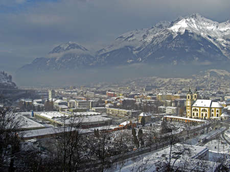 panoramatic: View on the city of Innsbruck during winter season with snow on the rooftops and the Alps in background the sky is a bit cloudy