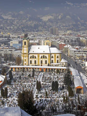 panoramatic: View on the city of Innsbruck during winter season with snow on the rooftops the sky is a bit cloudy