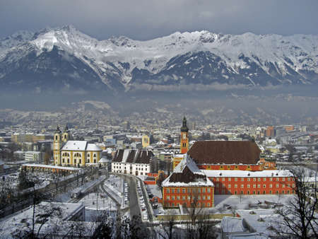 panoramic roof: View on the city of Innsbruck during winter season with snow on the rooftops and the Alps in background the sky is a bit cloudy