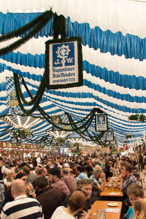wiesn: Traditional dressed people with dirndls and leather trousers in a beer tent on Theresienwiese celebrating with beer and music Editorial