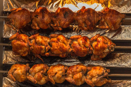 broiling: Broiling machine with lots of chicken turning to get brown and ready to serve Stock Photo