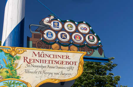 Maypole at Viktualienmarkt with a colored figure and the signs of the Munich beers to remind of the German purity law Editorial