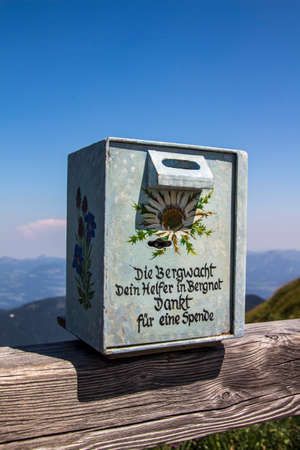 rescue service: Box for donations to the mountain rescue service on top of the Kehlstein, Obersalzberg with the mountains in the background