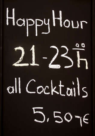 discounted: Happy hour sign in front of restaurant offering discounted cocktails for 5,50 Euro between 9-11pm