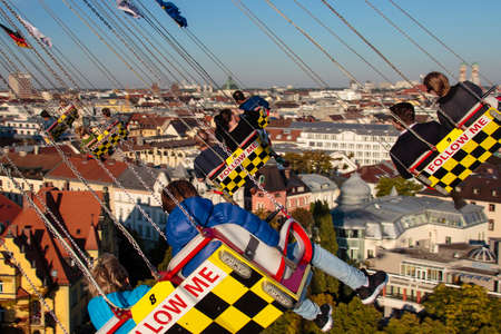chairoplane: Carousel in motion with people flying through the air on Theresienwiese Editorial