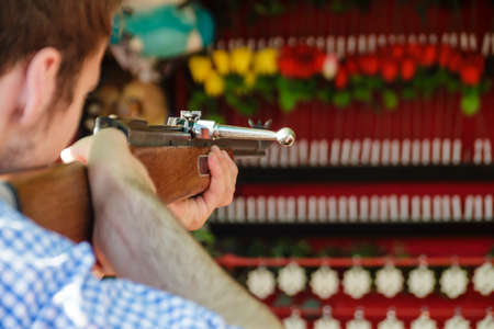Man at a shooting gallery trying to hit white stars